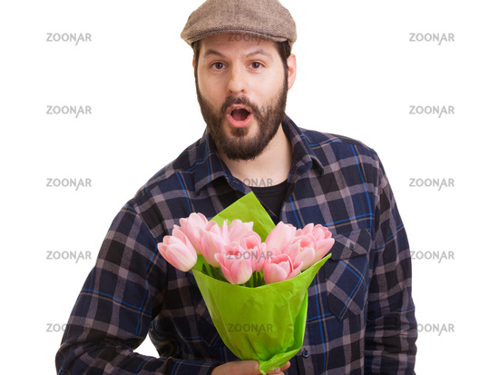 Bearded young handsome man holding a bouquet of pink tulips looking surprised, isolated on white background. Mothers day, Valentines day, Easter and surprise Concept.