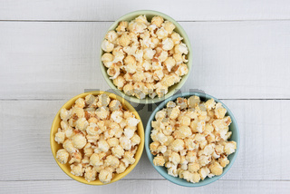 Overhead shot of three sifferent colored bowls filled with fresh popped popcorn, on a white wood table.