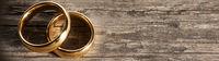 Golden wedding rings on wood