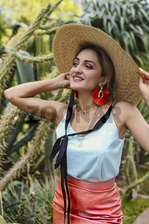 Stylish female model against green cactuses