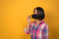 Cute young woman with face protective mask during quarantine. Isolated on yellow background. Virus outbreak concept