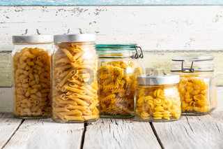 Various types of raw italian pasta in jars.