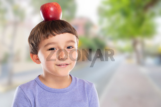 Young boy child with red apple fruit on his head town copyspace copy space healthy eating concept