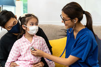 Doctor visit and examine by listen to heart of child girl patient at home.