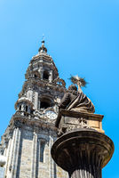 Sculpture of Apostle St. James against the tower of Cathedral of Santiago on blue sky