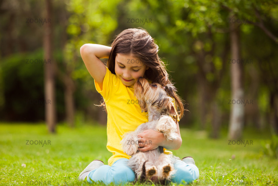 Little girl with a pet in the yard