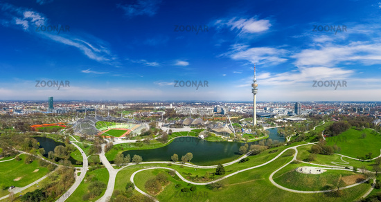 A wonderful spring day in Munich Olympiapark from above as a drone shot with a blue sky.