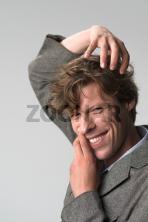 Young handsome man smiling positively and confidently posing with hands on his face and head, looking satisfied, friendly and happy against grey background. Facial expressions, emotions, feelings
