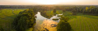 Nature scenery from aerial perspective with river and mowed meadow at sunset