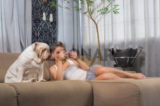 Young woman using smartphone on sofa with pet dog (english bulldog)