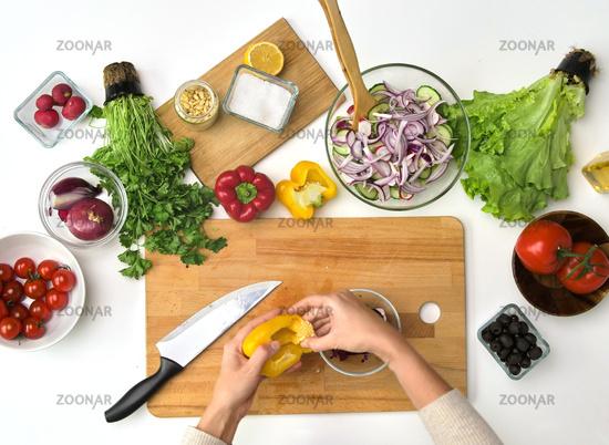 hands preparing pepper for salad at kitchen