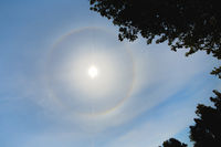 Atmospheric optical effect circle around the sun on hot summer day. Atmospheric halo phenomenon arou