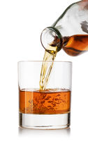 whiskey poured into a glass from a bottle