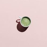 Flat lay of matcha tea on pink