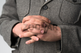 A young businessman putting his hands together on his chest listens intently to his opponent. A young guy in a business jacket stands cross-handed with his fingers all in attention