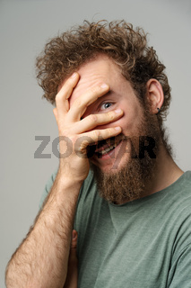 Shy handsome young man covered his face with hand pry with his eye, curly hair in olive t-shirt isolated on white background. Portrait of smiling young man