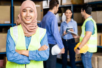 Islam Muslim female warehouse worker portrait with her team