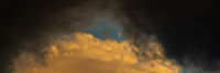 Panoramic view of dramatic storm clouds illuminated rising of sun floating in blue sky