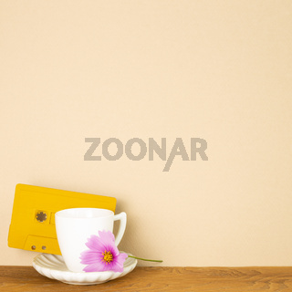 Coffee cup with audio cassette tape and common cosmos flower on wooden table with beige background. Autumn concept