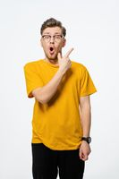 Handsome young man pointing finger sideways in eye glasses shocked with surprise expression on his face.Young casual man portrait isolated on yellow background