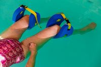 Senior woman leg with float in swimming pool
