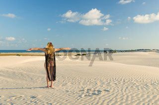 Young woman landing on the sand dunes of Mangue Seco beach located in Bahia.