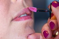 Applying lipstick to a woman's lips