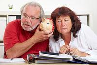 Senioren lauschen an Sparschwein