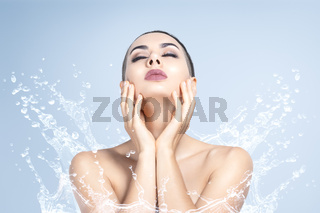 Young beautiful woman portrait with water splashes. Body and skin care wash in bathroom or showering concept