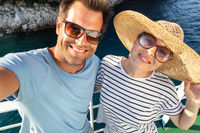 Beautiful, romantic caucasian couple taking selfie self portrait photo on summer vacations traveling by cruse ship ferry boat.