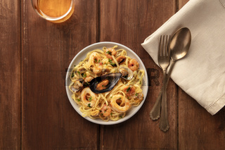 Seafood pasta. Tagliolini with mussels, shrimps, clams and squid rings, with a glass of wine, shot from the top on a dark rustic wooden background