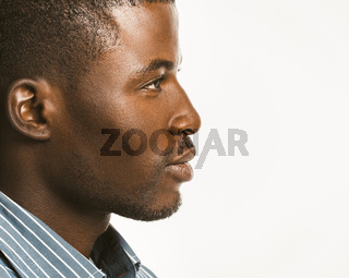 Serious African american man looks confident. Close up profile of Attractive Dark-skinned guy isolated on white background. Copy space at right side. Toned image