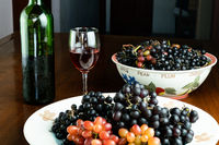 Freshly harvested red grapes and black grapes in ceramic plate with red wine in a glass.