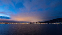 Approaching the illuminated norwegian city Trondheim in early dawn seen from the sea on cruise ship