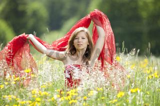Junge Frau mit rotem Tuch in einer Blumenwiese