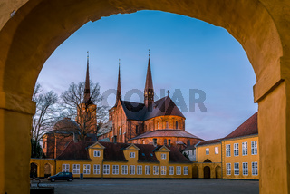 Roskilde cathedral in the soft evening light under the yellow portal of Roskilde Palace