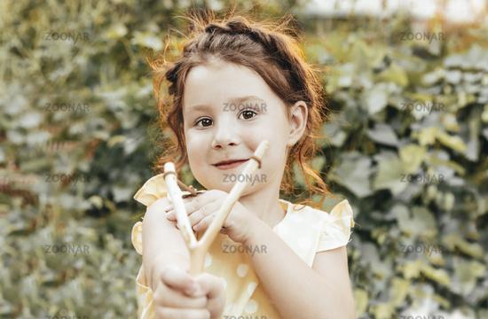 Ginger girl with slingshot in garden