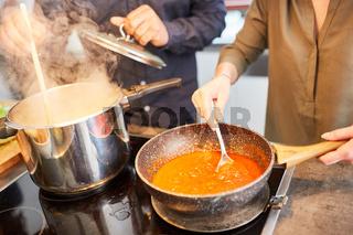 Paar kocht Nudeln mit Tomatensauce in Küche zu Hause