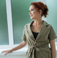 Woman in nice khaki pantsuit near window in studio
