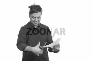 Studio shot of crazy Caucasian businessman cutting paper