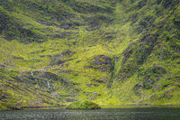 Green island on Lough Callee and waterfalls on mountainside of Carrauntoohil mountain