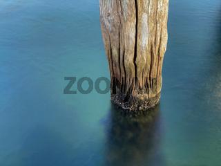 Alter faltiger Holzpfahl im Wasser - Langzeitbelichtung