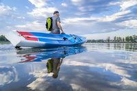 senior stand up paddler on a lake
