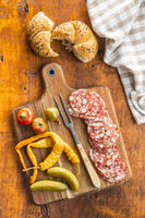 Sliced italian salami with hazelnuts, pickled chili peppers and pickles