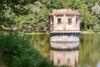 an old abandoned structure on a pond, turret with a shutter on a forest pond