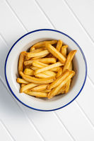 French fries in bowl on white table.