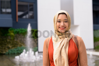 Happy young beautiful Indian Muslim woman smiling in the city outdoors
