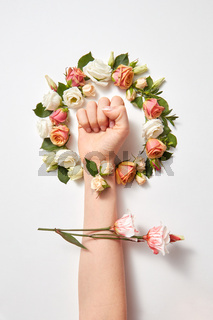 Fresh natural flowers wreath with female's hand.