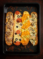 Composition of hot tasty baked sandwiches with various toppings. Cheese, tuna, mozarella, spices