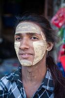 Yangon, Myanmar, Portrait eines jungen Mannes mit Thanakapaste Make-up im Gesicht